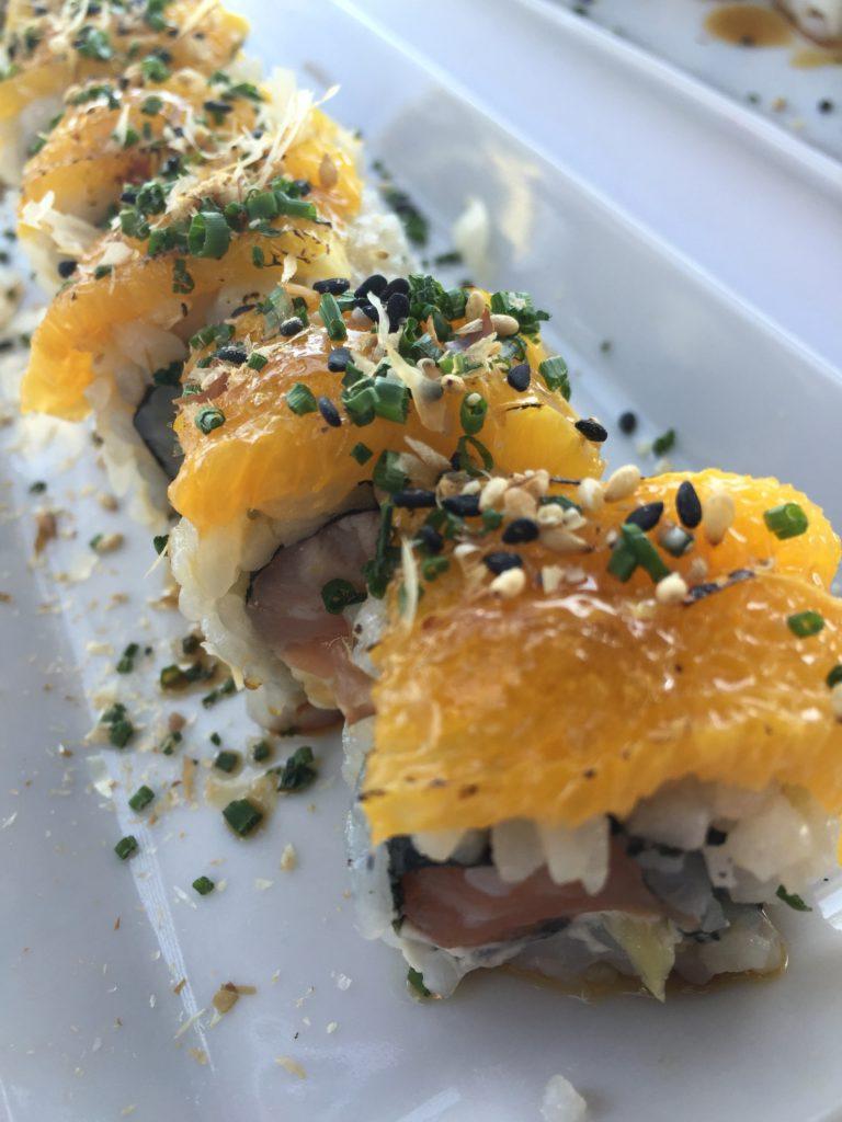 Sushi design:  рыба, рис и ягоды на скале над океаном.